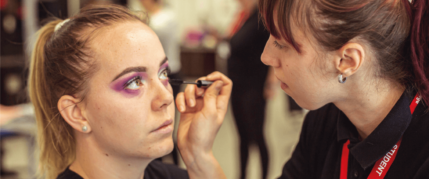 Student putting makeup on a client