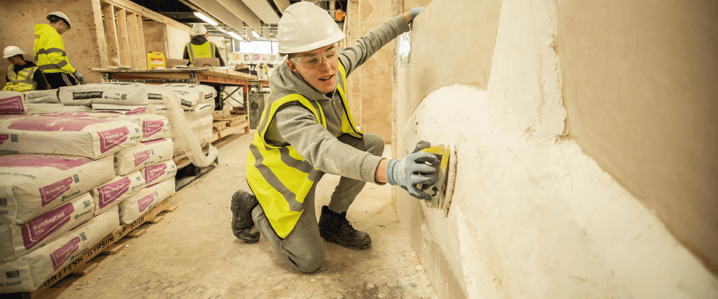 Student plastering a wall