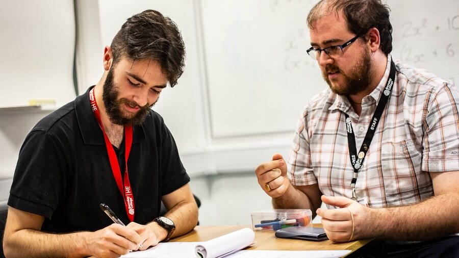 A tutor offers advice and guidance to a student