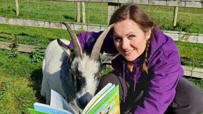 Lindsey Robinson reading to a goat.