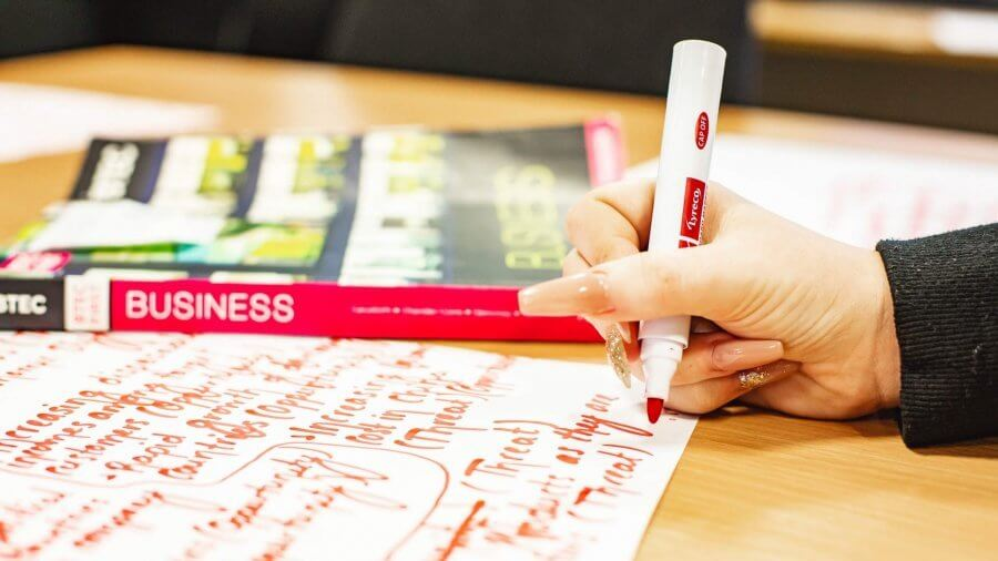 A hand making notes with a thick marker pen on a large piece of paper. There is a textbook entitled 'business' in the background.