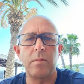 photograph of a bald man with glasses, stood in front of a beach background