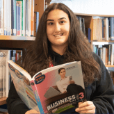 a young girl with dark hair and eyes smiles at the camera - she is in a library and holding a textbook about business