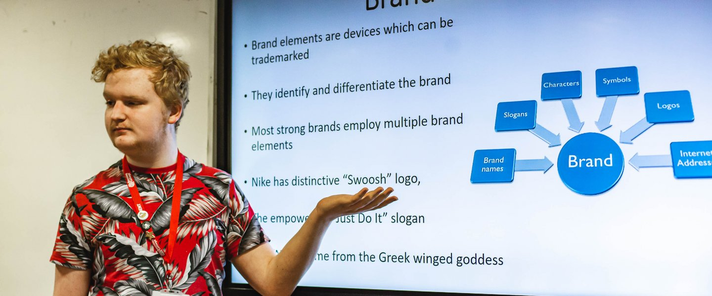 A teenage male student wearing a bright lanyard and a t-shirt gestures to a smart board, which has a presentation reading 'brand elements'